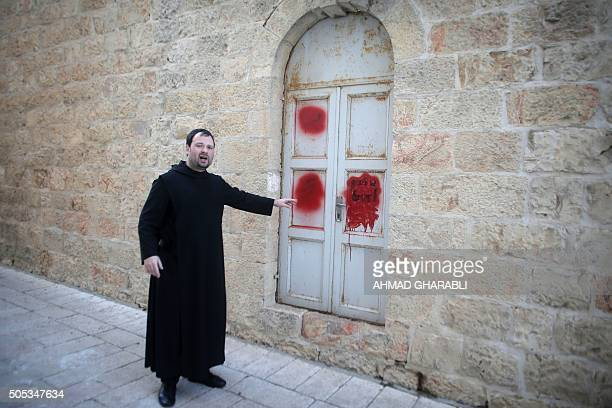 Father Nikodemus Schnabel spokesperson of the Dormition Abbey points towards antiChristian graffiti in Hebrew daubed on the Church of the Dormition...