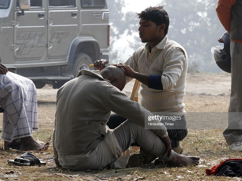 Father of Delhi Gang Rape victim getting his head shaved off at his native village as whole village is getting facelift ahead of Akhilesh Yadav's on January 10, 2013 in Ballia, India. Uttar Pradesh administration is working overtime to prepare for Chief Minister Akhilesh Yadav's expected visit on January 12 to give a cheque to the father of the gangrape victim who died in Singapore after being brutally raped and tortured on a bus.