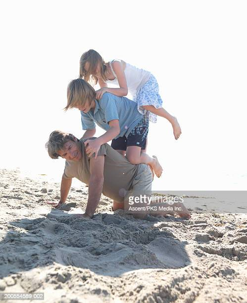 Father on all fours with two children (11-14) on back on beach