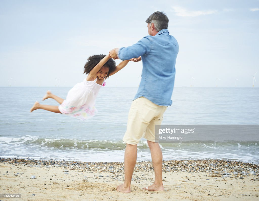 Father on beach swinging daughter around. : Stock Photo
