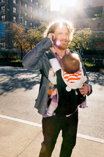 Father on cell phone and carrying baby