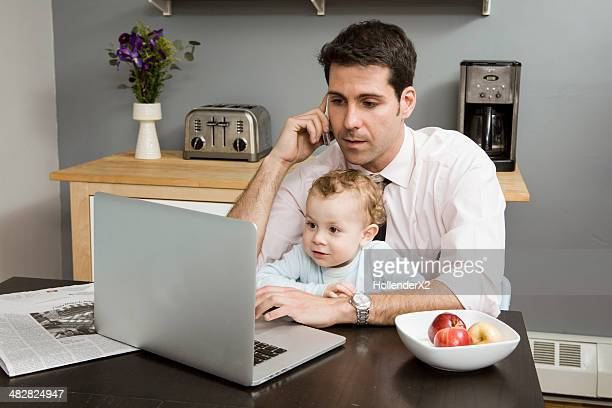 Father on phone and computer while son is on lap