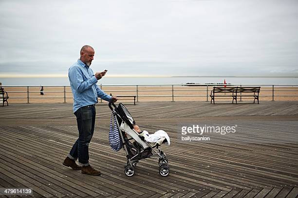 Father On Phone With Son In Stroller.