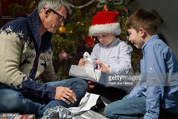 Father on sitting room floor opening christmas gifts with two sons