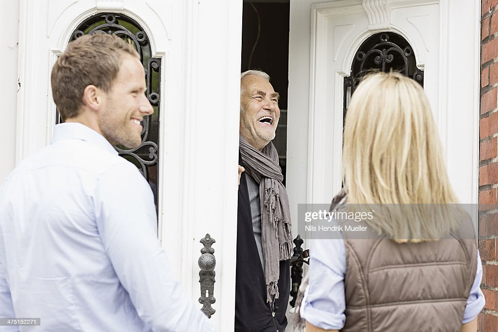 Father opening front door laughing