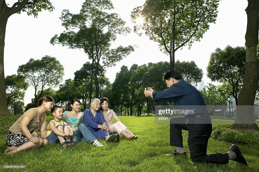 Father photographing family in park : Stock Photo
