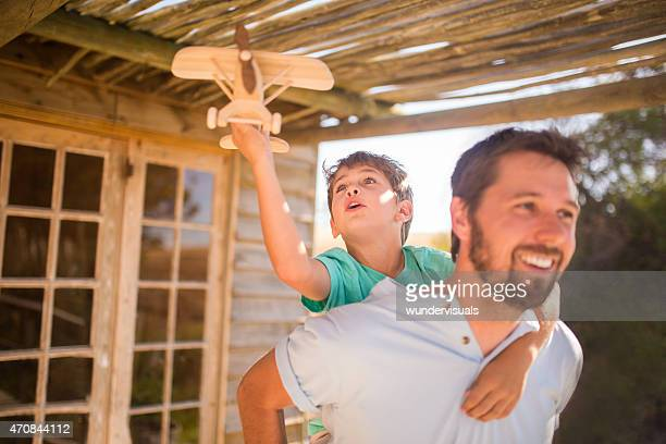 Father piggybacking his son playing with a toy wooden plane