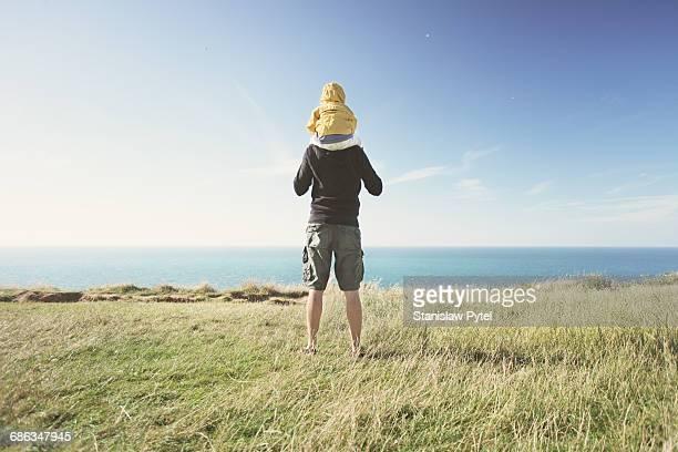 Father piggybacking kid near ocean