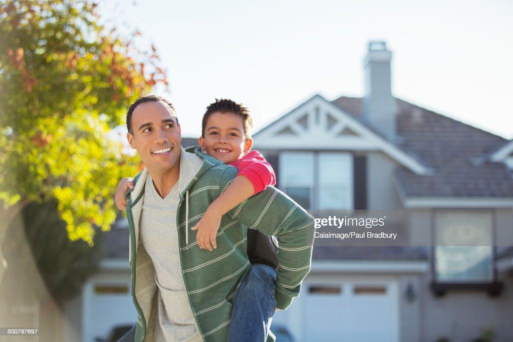 Father piggybacking son outdoors : Stock Photo