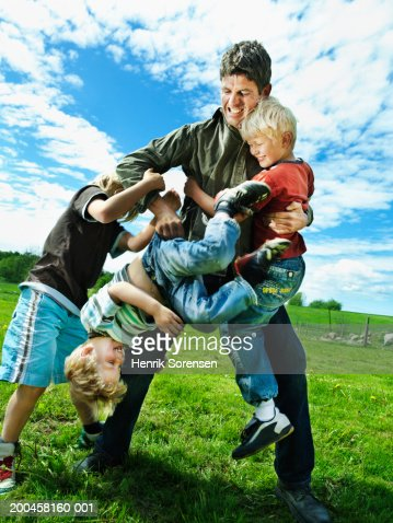 Father play fighting with three sons (4-9) in garden : Stock Photo