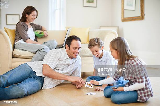 Father playing a card game with kids (8-11) with mother using laptop on couch