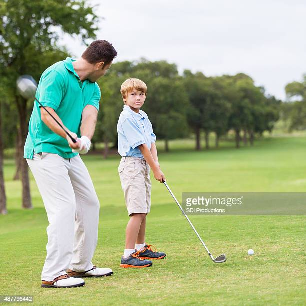 Father playing golf with his young son