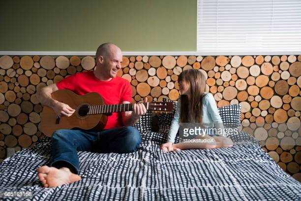 Father playing guitar for his daughter
