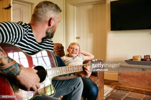Father playing guitar with son at home