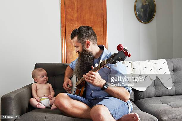 Father playing music to baby son at home