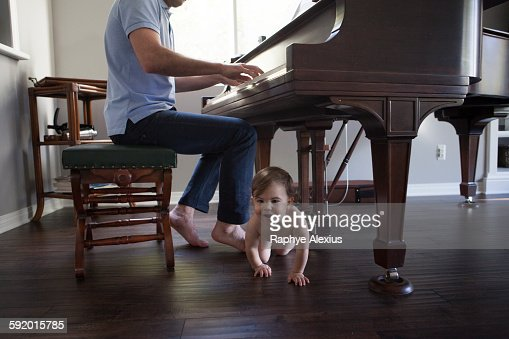Father playing piano with baby boy crawling at feet