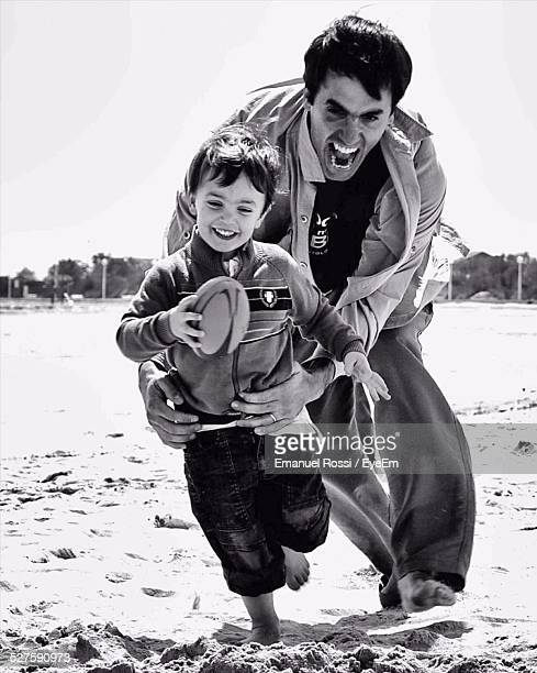 Father Playing Rugby Game With Son On Beach