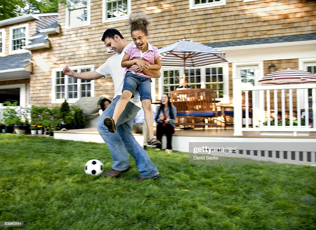 Father playing soccer with daughter in backyard : Stock Photo