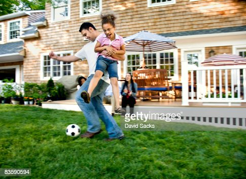 Father playing soccer with daughter in backyard