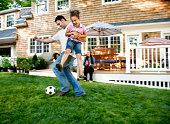 Padre jugando al fútbol con hija en jardín