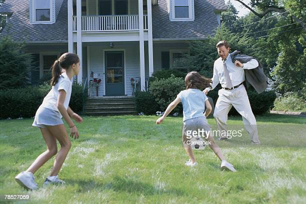 Father playing soccer with daughters