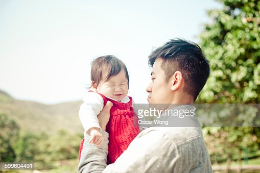 Father playing with baby girl in park