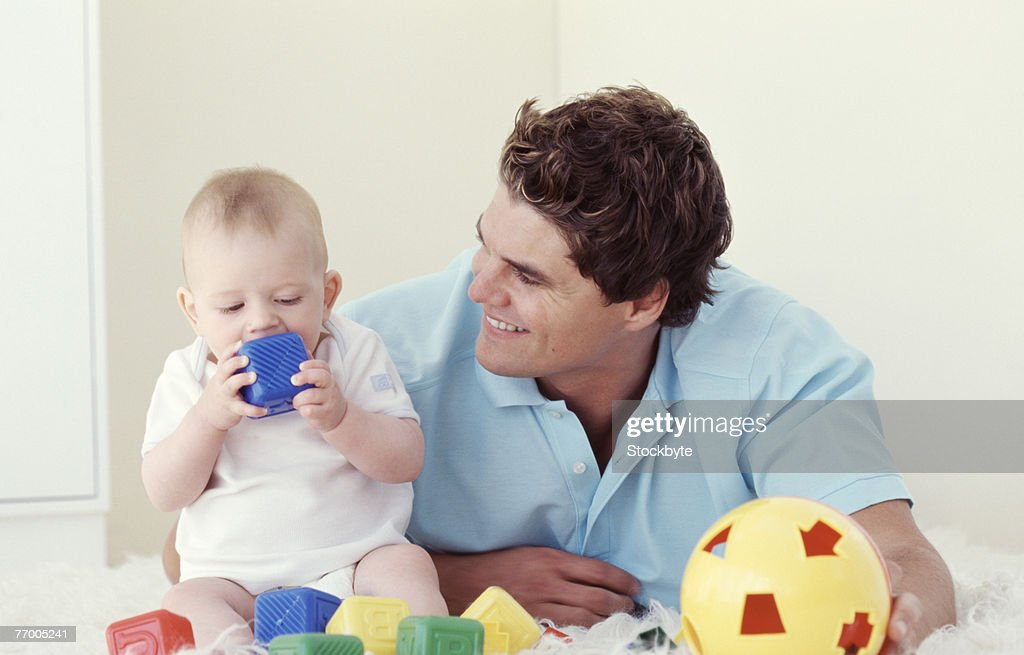 Father playing with baby (6-12 months), indoors : Stock Photo
