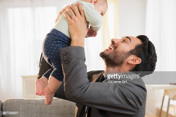 Father playing with baby on sofa