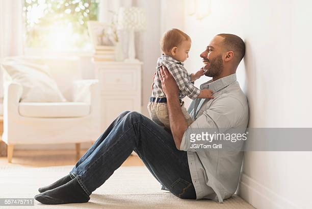 Father playing with baby son on floor