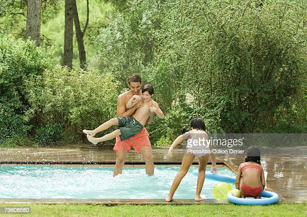 Father playing with children in swimming pool