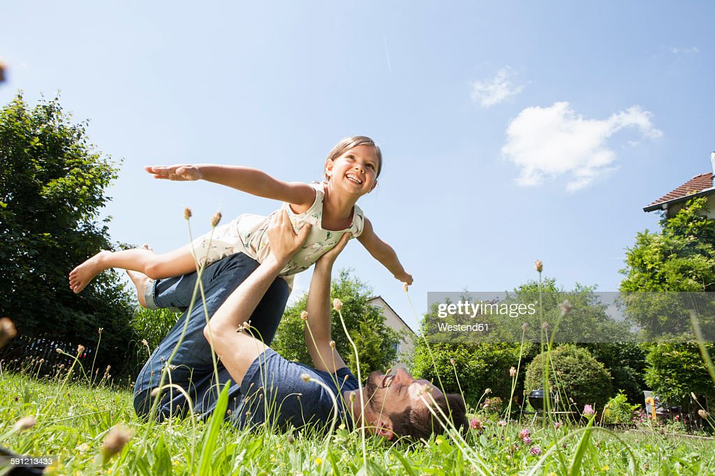 Father playing with daughter in garden : Photo