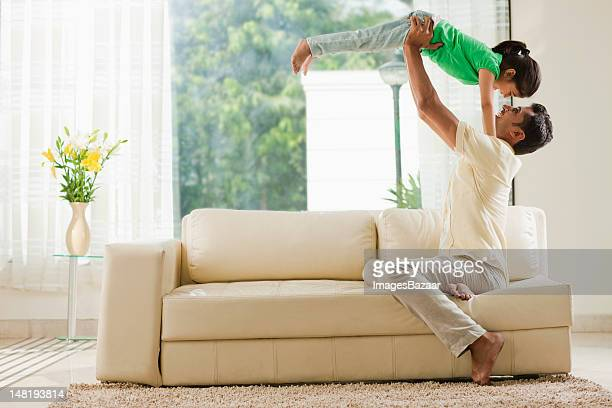 Father playing with daughter (6-7) in living room