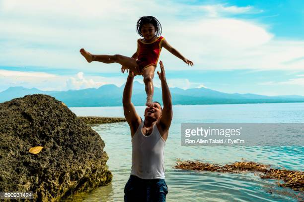 Father Playing With Daughter While Standing At Beach Against Sky