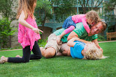 Father playing with his daughters in garden