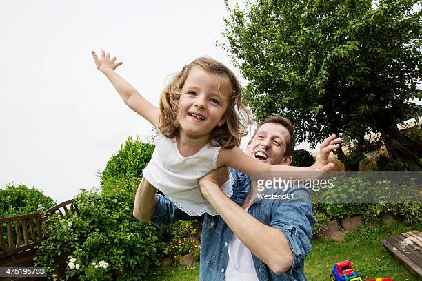 Father playing with his little daughter in the garden