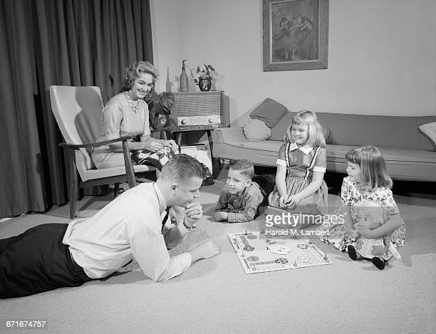 Father Playing With Kid While Mother Sitting In Living Room