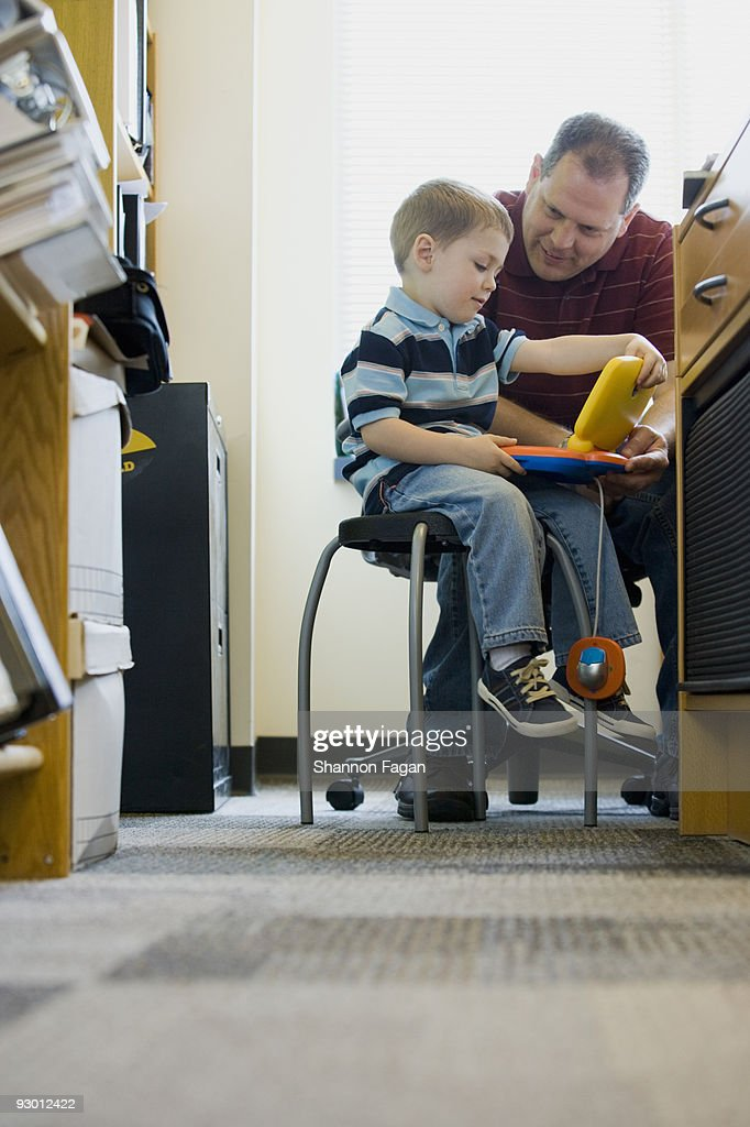 Father playing with son in office : Stock Photo