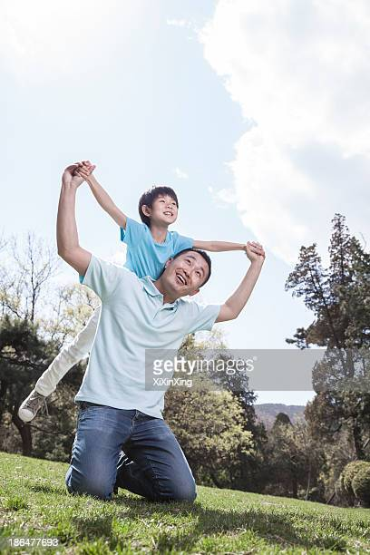 Father playing with son in park.