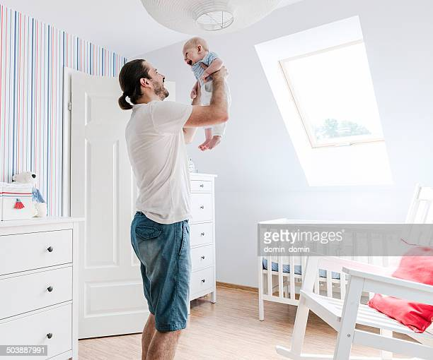 Father playing with son, smiling to him, raising child up