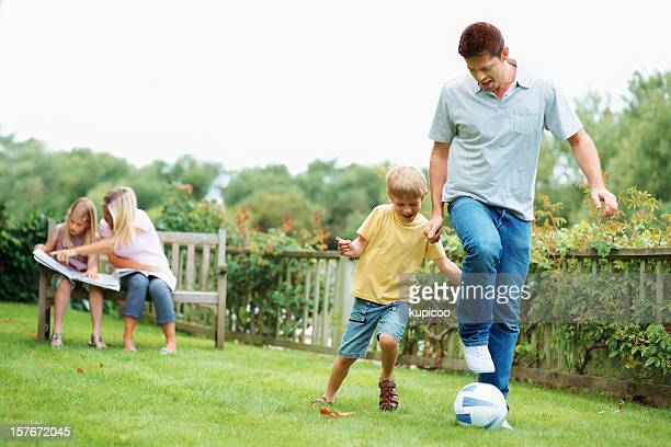 Father playing with son while mother and daughter sitting together