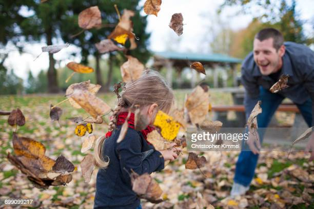 A father plays in the leaves with his daughter.