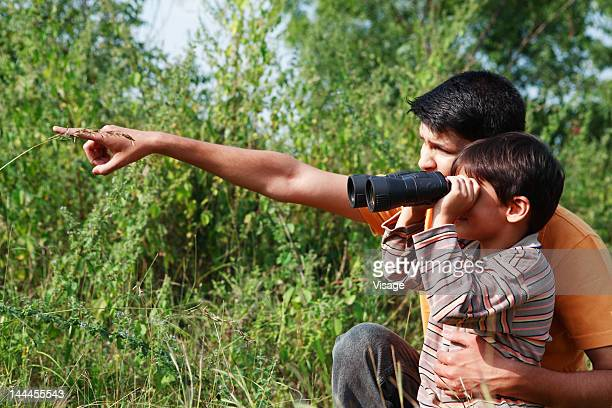 Father pointing, boy looking through binoculars