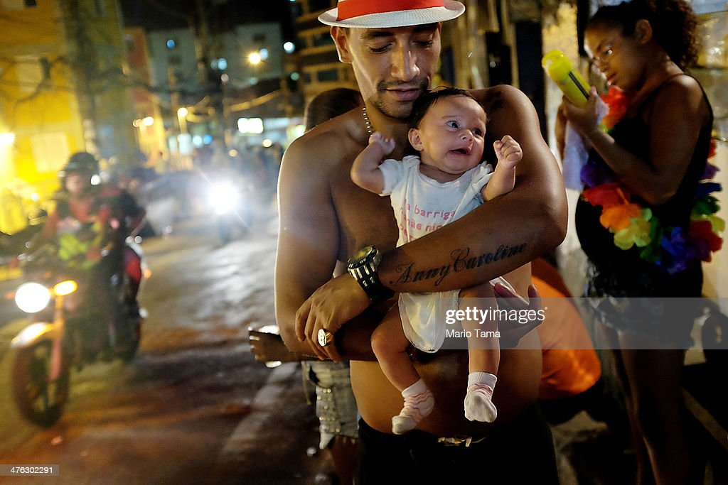 A father poses holding his baby Anny Caroline, tattooed on his arm, during a street carnival bloco in the Rocinha community, or favela, on March 2, 2014 in Rio de Janeiro, Brazil. Carnival is the grandest holiday in Brazil, annually drawing millions in raucous celebrations.