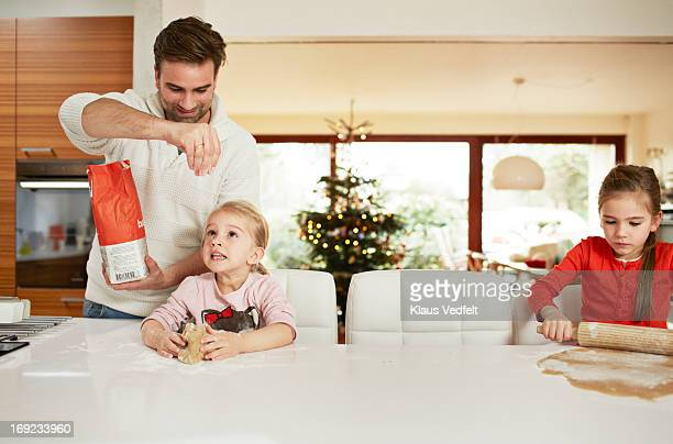Father pouring flour on daughters dough