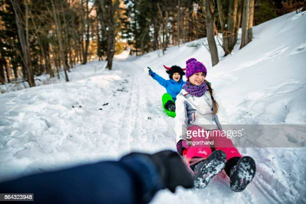 Father pulling children on sleds in winter forest