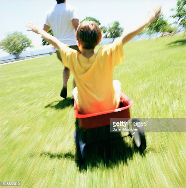 Father Pulling his Son in a Red Wagon