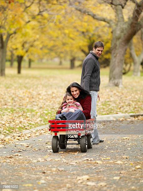 Father pulling mother and daughter in wagon
