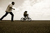 Father pursuing young cyclist learning to ride