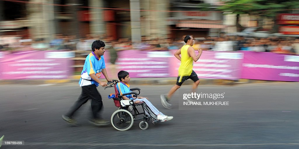 A father pushes his paraplegic son as he takes part in the Mumbai Marathon on January 20, 2013. Thousands of people turned out on a cool morning to take part in the annual race in the Indian city. AFP PHOTO/Indranil MUKHERJEE