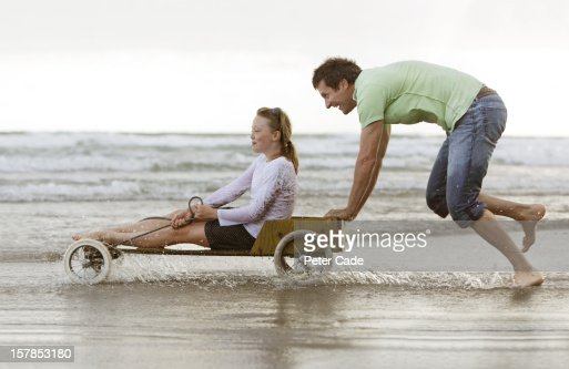 Father pushing daughter in go-kart on beach : Stock Photo